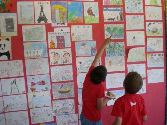 Dos nens busquen els seus dibuixos entre tots els participants al Concurs de Dibuix